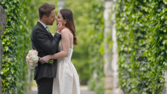slo mo newlyweds caressing one another in ivy covered passageway - dinner jacket stock videos & royalty-free footage