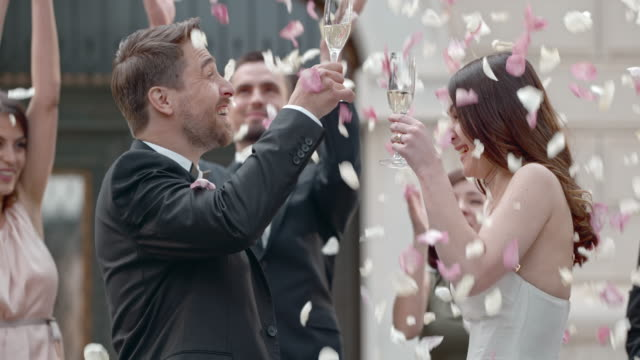 SLO MO Newlyweds clinking glasses in rose petal shower