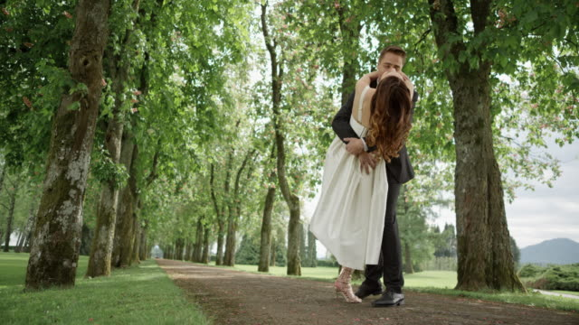 SLO MO DS Newlyweds dancing in the park and kissing