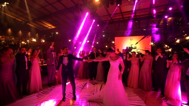 newlyweds dancing while wedding guests holds sparkles - nightlife stock videos & royalty-free footage