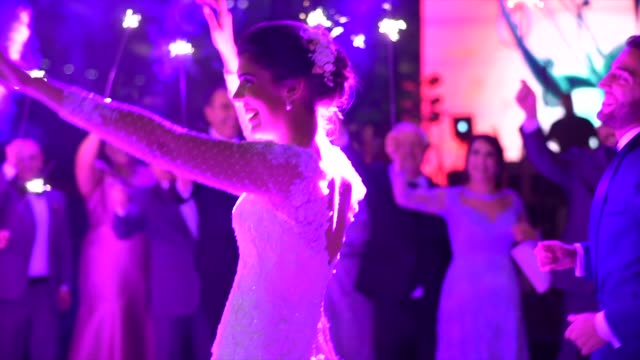 newlyweds dancing while wedding guests holds sparkles - bridegroom stock videos and b-roll footage