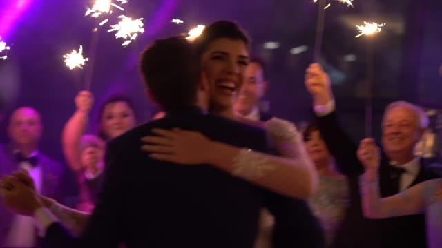 stockvideo's en b-roll-footage met jonggehuwden dansen terwijl bruiloft gasten houdt sparkles - bruidegom