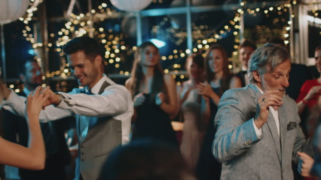 vídeos de stock e filmes b-roll de newlyweds dancing with guests at wedding party - casamento