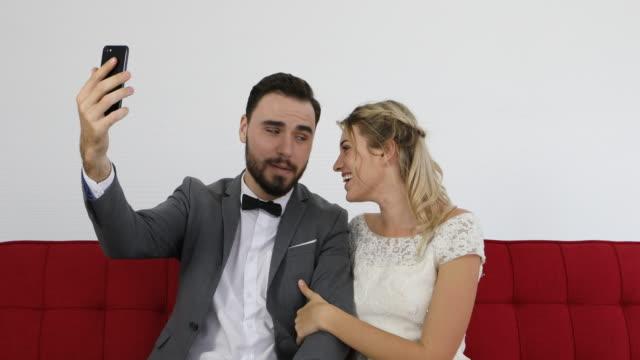 jungvermählten fröhlich brautpaar smartphone selfies fotografieren und lächelnd - suspenders stock-videos und b-roll-filmmaterial