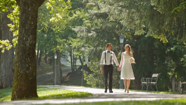 SLO MO Newlyweds holding hands while walking in a park