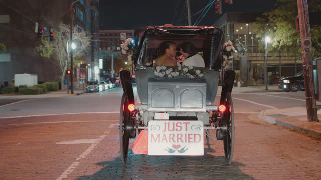 newlyweds kiss as they ride off into the night in a horse-drawn carriage - eternity stock videos & royalty-free footage