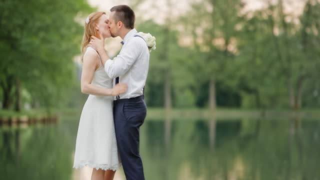 Newlyweds kissing and dancing by the lake