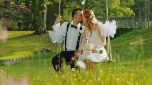 SLO MO DS Newlyweds kissing on a swing in nature