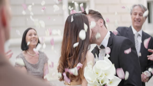 vídeos de stock e filmes b-roll de slo mo newlyweds kissing while guests throw petals on them - casamento