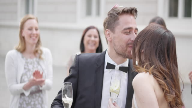 slo mo newlyweds kissing while holding glasses of sparkling wine - just married stock videos and b-roll footage