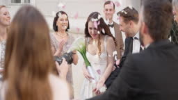 SLO MO DS Newlyweds leaving church in rose petal shower