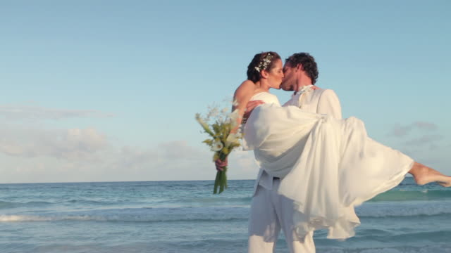 Newlyweds on beach, groom lifting up bride and spinning her round