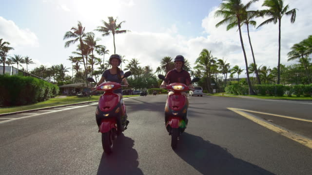 newlyweds ride mopeds together on a sunny day in hawaii - turtle bay hawaii stock videos & royalty-free footage