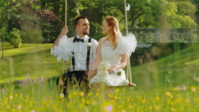 SLO MO DS Newlyweds sitting on a swing in sunshine