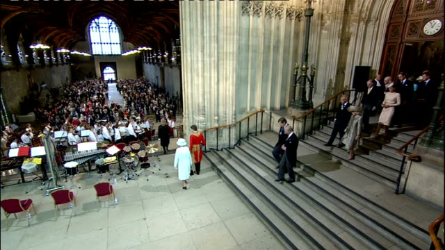 1200 1300 **Orchestral Music heard** Westminster hall INT Queen Elizabeth enters Westminster Hall as fanfare and orchestral music played/ Prince...