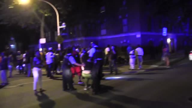 News footage of a chaotic crime scene in Chicago where two people were shot a large crowd gathered and police attempted crowd control