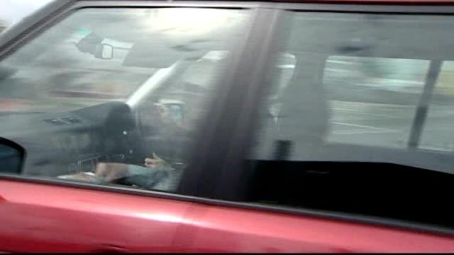 news of the world hacking scandal: rupert murdoch arrives in london; ext car carrying murdoch driven along past - itv weekend late news点の映像素材/bロール