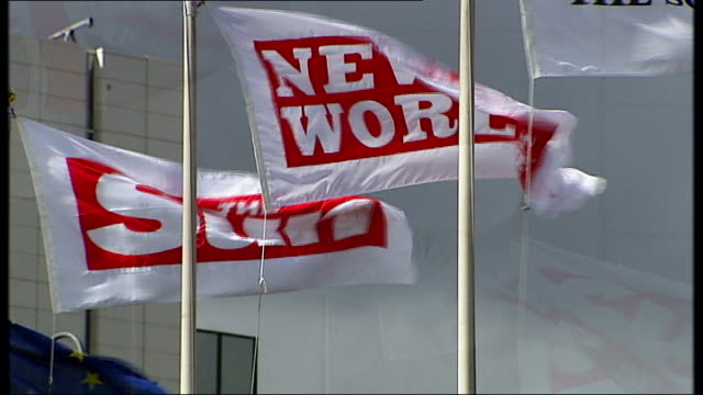 'news of the world' phone hacking scandal grows ext flags flying outside news international headquarters entrance to news internation hq with the sun... - 盗聴点の映像素材/bロール