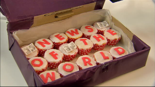 news of the world phone hacking scandal: latest developments; wapping: editorial staff at work in news of the world newsroom cupcakes with icing... - 黒のシャツ点の映像素材/bロール