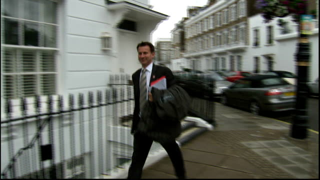 news of the world phone hacking scandal: news of the world paper to close; england: london: jeremy hunt mp along street - news of the world stock-videos und b-roll-filmmaterial