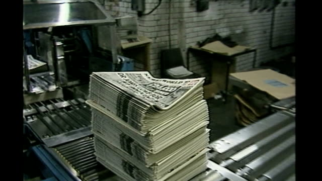 news of the world phone hacking scandal: news of the world paper to close; 'news of the world' newspapers along on conveyor graphicised sequence... - news of the world stock-videos und b-roll-filmmaterial