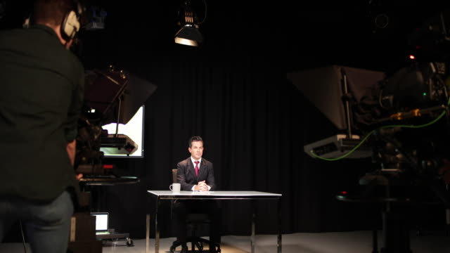 vídeos de stock, filmes e b-roll de news presenter in a tv broadcasting studio - reportagem imagem