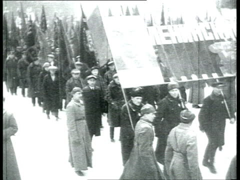 news special issue, xvii communist party of the soviet union congress, parade on red square in snow, people with banners, stalin wearing ushanka... - 1934 stock-videos und b-roll-filmmaterial