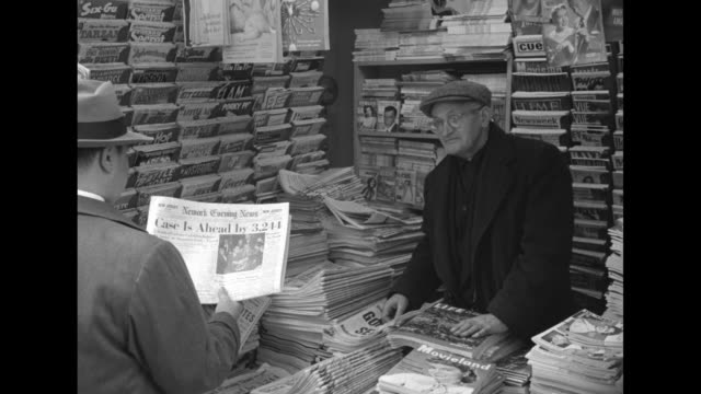 vidéos et rushes de news vendor inside his stand with customer holding paper case is ahead by 3241 / hand displays front pages of newspapers newark star ledger howell... - vendeur ambulant