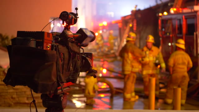 a news video camera filming firefighters fighting to put out a house fire at night in a neighborhood. - camera photographic equipment stock videos & royalty-free footage
