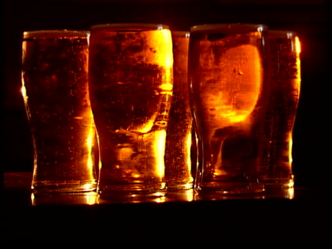 news video wall generics library: part one; **bar room chat and intermittent pop music over following shots** pints of beer - lager - lined up on bar... - lager stock videos & royalty-free footage
