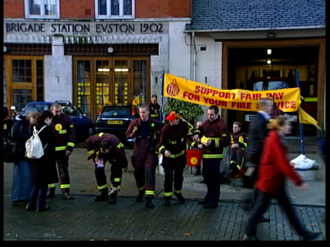 part one int fire engine towards into station firefighters in uniform on strike outside station in front of banner 'support fair pay for your fire... - itv news at one stock videos & royalty-free footage