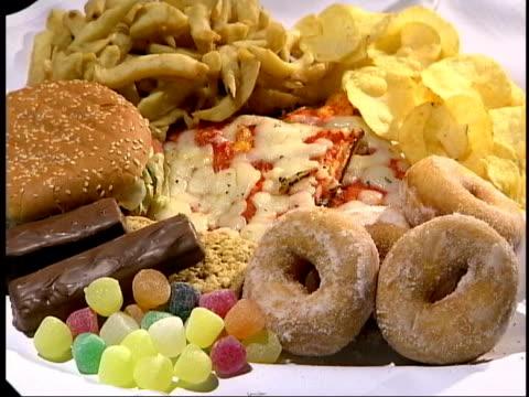 vídeos de stock, filmes e b-roll de part one plate full of unhealthy food burger doughnuts chips sweets and pizza basket of healthy fruit including appleas oranges grapes and bananas - estilo de vida insalubre
