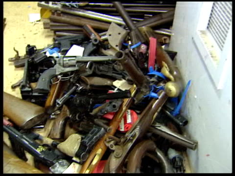part two siezed guns handguns displayed in box and on table siezed weapons guns and rifles on floor/ close shots of gun barrels close up of uk... - man and machine stock videos & royalty-free footage