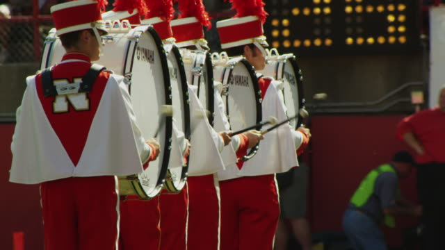 news videographer shoots the drum percussion section marching and performing during half time at a football game. - marching band stock videos and b-roll footage