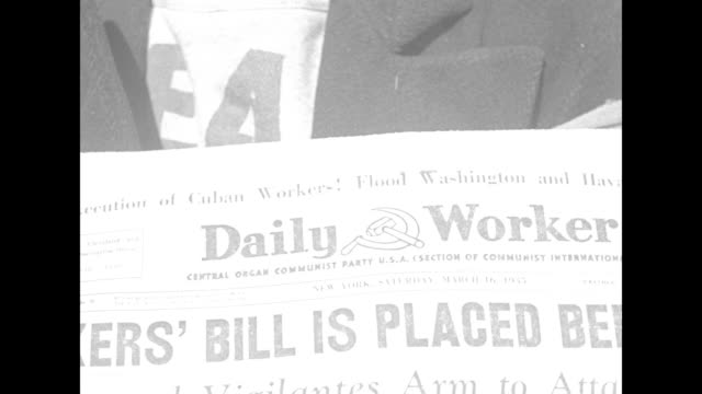 Newsboy at Union Square with dangling cigarette handing out copies of Daily Worker / close look at front of newspaper with hammer and sickle logo/...