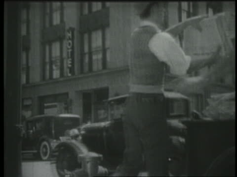 vidéos et rushes de b/w 1939 newsboy runs up to truck, grabs stack of newspapers + starts shouting to sell papers - 1930 1939