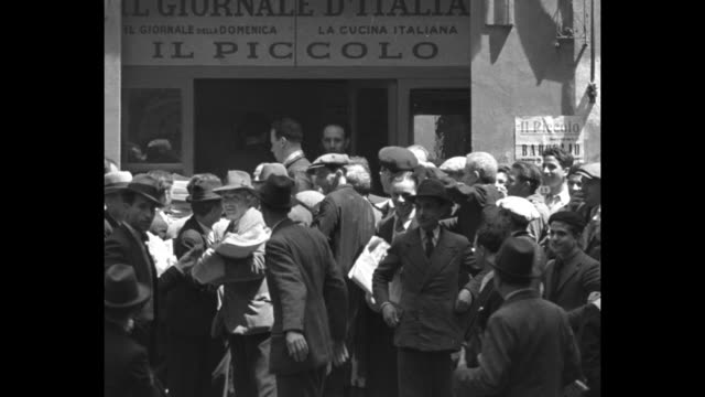 newsboys and men shouting in italian about second italo-ethiopian war and distributing papers among crowd / men hoisting flag of kingdom of italy... - hoisting stock videos & royalty-free footage