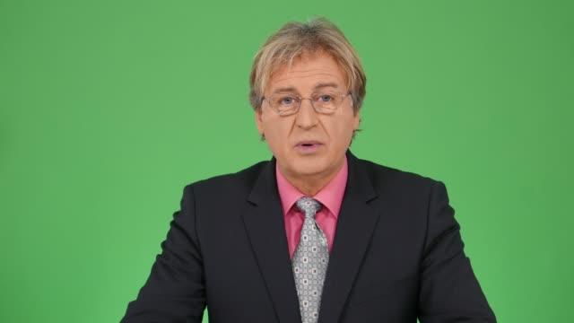 vídeos de stock e filmes b-roll de 4k newscaster reading the breaking news - evento de notícias