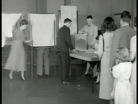 vídeos de stock, filmes e b-roll de newspaper 'assembly passes school board bill.' int virginia people lined up to vote at poll booths. citizen's on line. two women talking at table.... - filme documentário