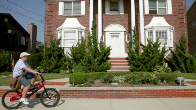Newspaper boy on bike throwing newspaper into front yard