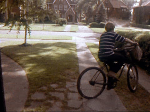 1970 newspaper boy riding bicycle tossing newspaper onto front porch of house - suburban stock videos & royalty-free footage