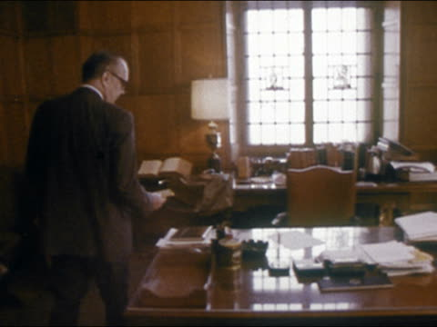 1970 newspaper editor or publisher picking up mail from secretary/ sitting down at desk with newspaper