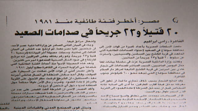 vídeos de stock, filmes e b-roll de newspaper headline declaring the worst sectarian strife since 1981. 20 dead and 23 injured in upper egypt clashes. article written by rami ibrahim. - publicação
