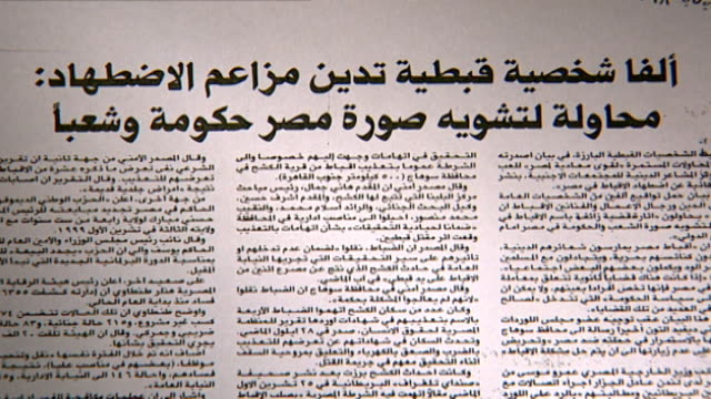 vídeos de stock, filmes e b-roll de newspaper headline. prominent copts refute allegations of persecution and attempts at distorting the image of egypt. in 2000, 21 copts were massacred... - publicação