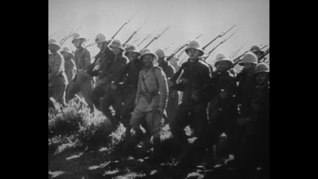 """newspaper headline reading """"rome armies gain in north and south, capturing 3 towns"""" / two shots of italian soldiers marching forward in formation /... - アフリカの角点の映像素材/bロール"""
