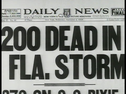 stockvideo's en b-roll-footage met newspaper headlines '200 dead in fla storm' vs 'overseas railroad' train on side derailed wood & debris near overturned cars. unrepairable. - 1935