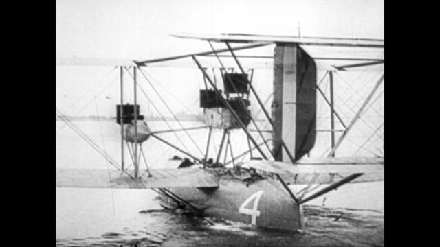 vidéos et rushes de newspaper headlines about first flight across the atlantic ocean in 1919 / men pushing the nc 4 flying boat out into the water / in 1953 admiral john... - 1910 1919
