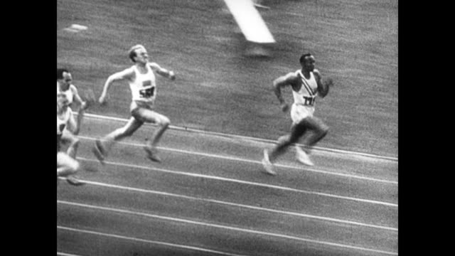 stockvideo's en b-roll-footage met / newspaper headlines reads 'negro athletes star in berlin olympics' / at the berlin olympic games / huge crowds in the packed stadium / athletes... - 1936