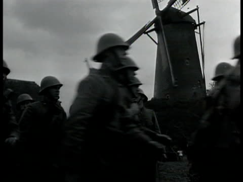 Newspaper 'Holland on Alert' MS Soldiers marching in town windmill BG WS Soldier patrolling dam HA Water running under bridge sandbags BG WS Car at...