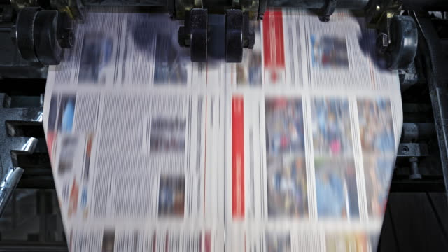slo mo ld newspaper pages being cut in the printing factory - pressa da stampa video stock e b–roll